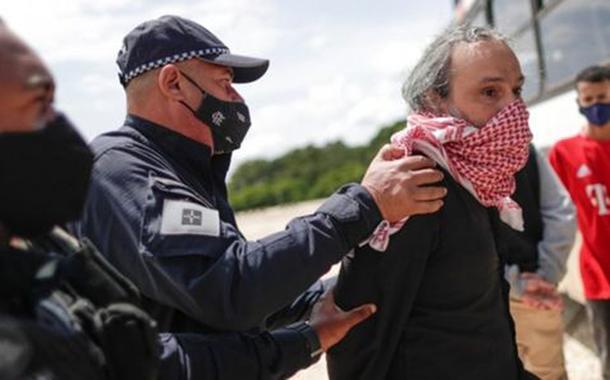 Manifestante é preso após fazer protesto contra Bolsonaro usando bandeira com suástica.