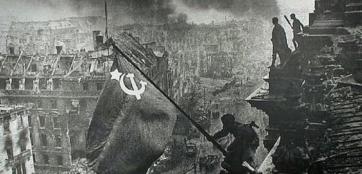 A bandeira soviética içada no telhado do Reichstag, foto histórica de Yevgeny Khaldei