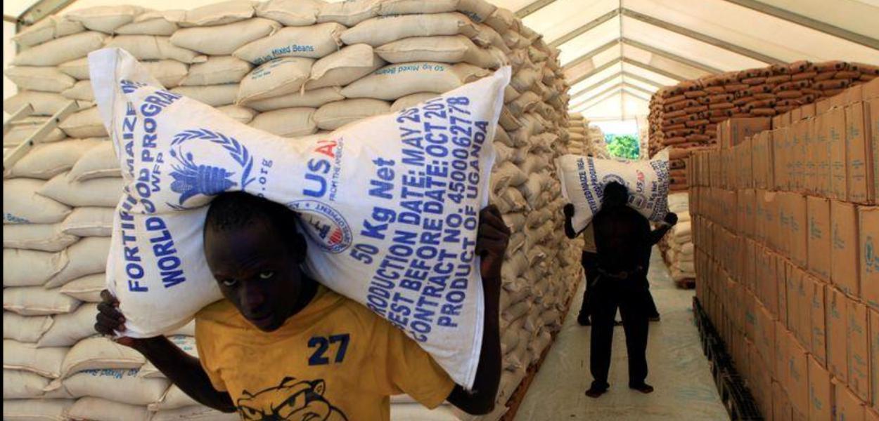 Pessoas carregam sacos de alimentos do Programa Mundial de Alimentos da ONU em assentamento para refugiados do Sudão do Sul em Uganda