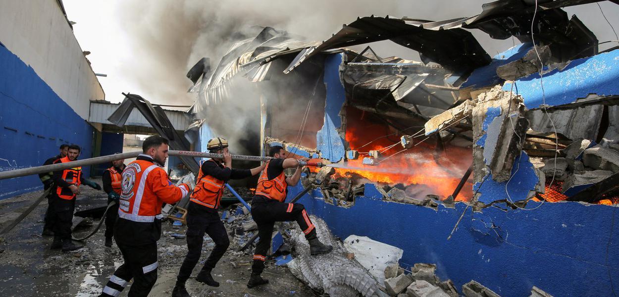 Bombeiros palestinos apagam chamas de fábrica atingida por míssil de Israel