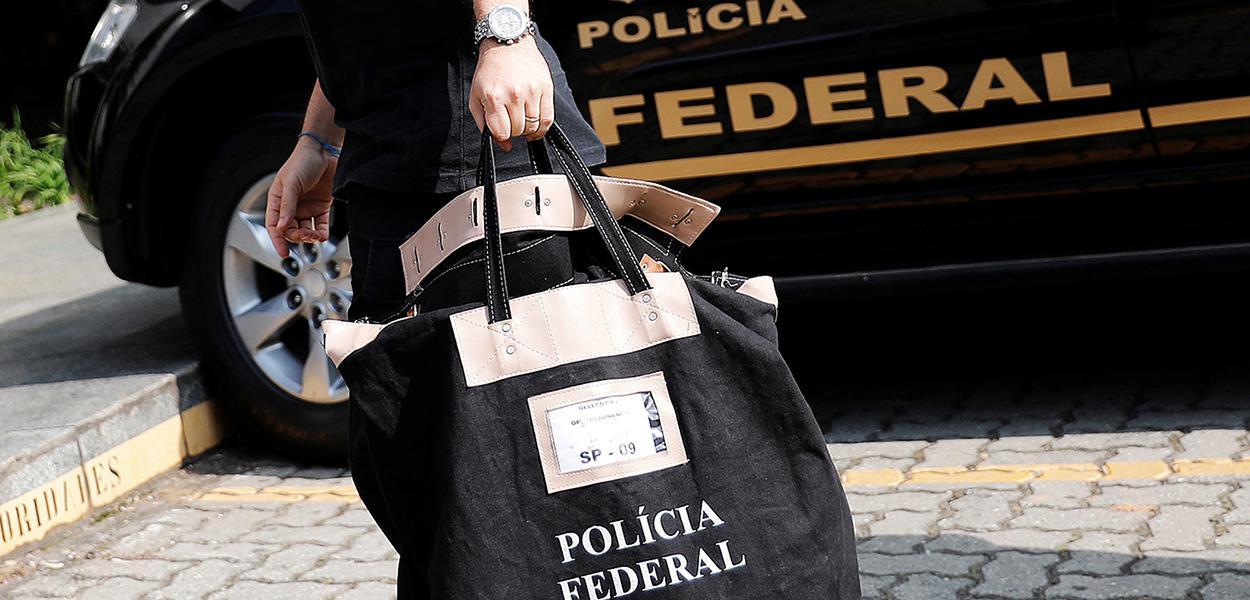 Policial federal carrega uma bolsa ao chegar à sede da Polícia Federal em São Paulo