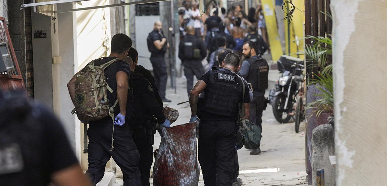 Policiais carregam corpo durante operação na favela do Jacarezinho 06/05/2021