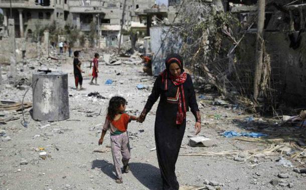 Palestina caminha com criança por prédios destruídos ao norte da Faixa de Gaza