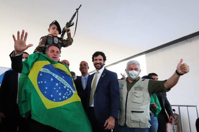 Bolsonaro se enrola na bandeira nacional para foto com criança segurando arma de brinquedo