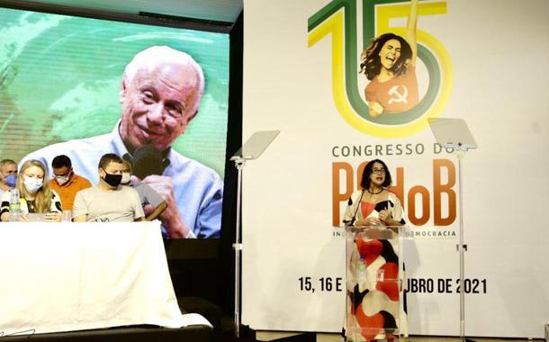 Luciana Santos, presidente do PCdoB fala no 15º Congresso. No painel, ao fundo, imagem de Haroldo Lima, dirigente do partido falecido em março último, homenageado no encontro