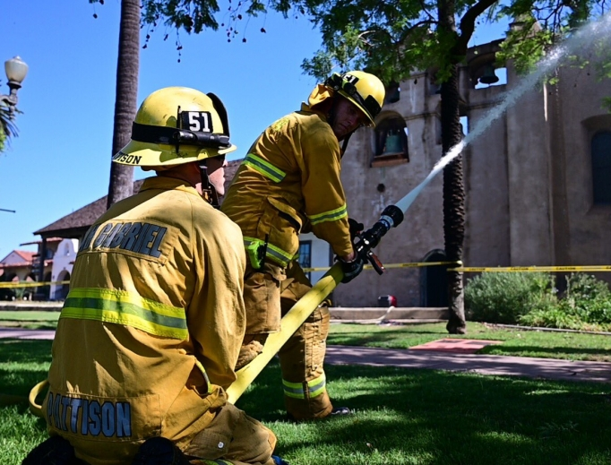 Firefighters try to extinguish a rooftop fire at San Gabriel Mission.