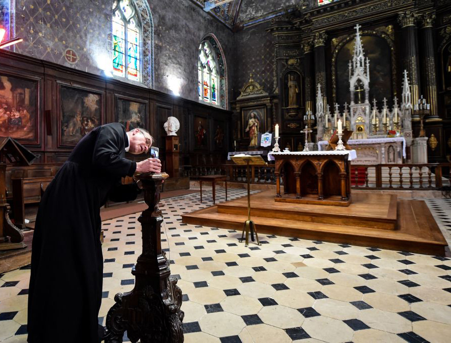 Father Olivier Monnier installs his mobile phone on a wooden candlestick as he prepares to broadcast the 11 o'clock Mass with a video chat smart phone application on April 3, 2020, at Saint-Jacques church in Illiers-Combray, France.