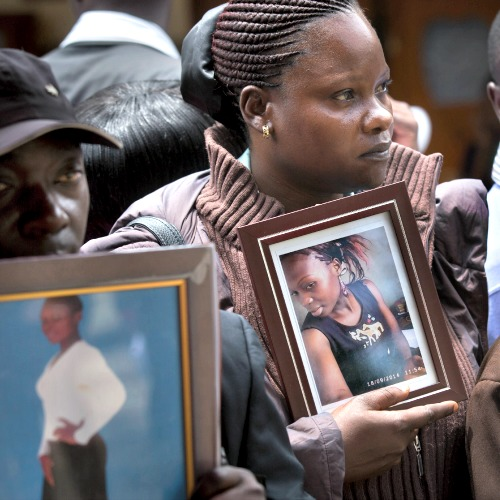 Cousin Teresa Apiyo (c) and an unidentified relative (l) hold photographs of student Selpha Aoko Wanda, 21, who was killed in last week's Garissa attack at the Chiromo Funeral Parlour in Nairobi, Kenya, on April 9.