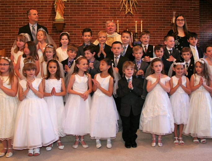 Father George DeVille and first communicants at Holy Rosary parish in Muse, Pennsylvania.