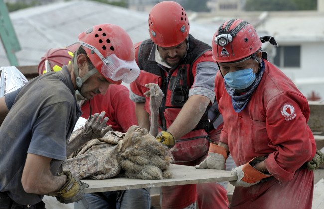 Members of a Mexican search-and-rescue team pull Anna Zizi alive Jan. 19 from the rubble in Port-au-Prince, Haiti, after the devastating Jan. 12 earthquake. She was rescued from the collapsed home of the parish priest at the Cathedral of Our Lady of the Assumption. Several of of the rescue workers were in tears as they pulled the woman free from tons of rubble.