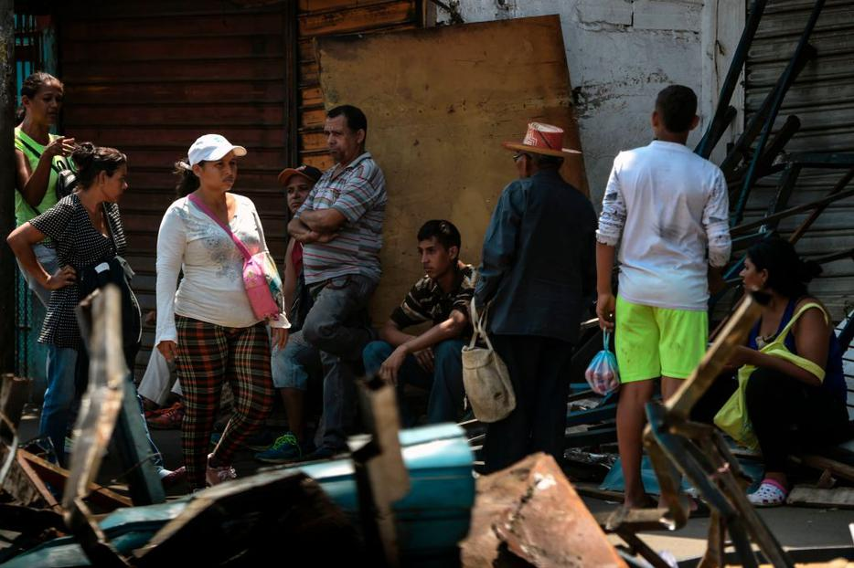 Locals sit and stand on the street March 13 in Maracaibo, in the border state of Zulia, during the massive blackout that has paralyzed Venezuela for days.