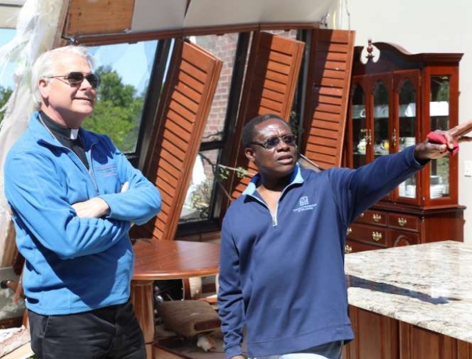 Archbishop Paul Coakley and Fr. Oby Zummas inspect damage at Holy Cross Catholic Church.