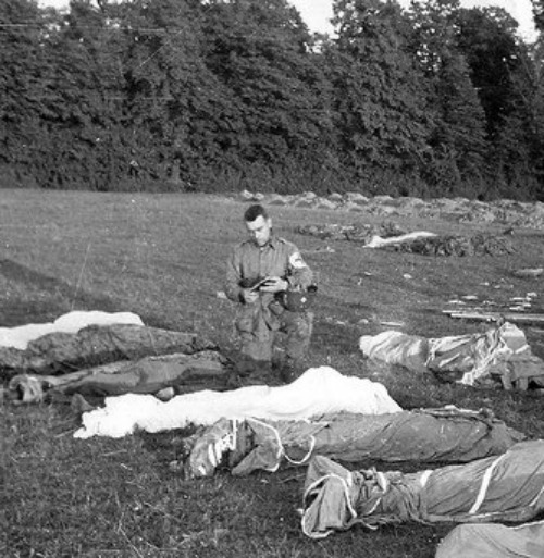 Father Francis Sampson, who was known as the 'Parachute Padre,' gives last rites to paratroopers killed in action during the D-Day invasion of Normandy.
