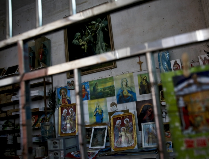 Catholic religious paintings and Bibles are displayed behind bars at an underground Catholic church in Jiexi county in south China's Guangdong province March 27. A group that monitors Christianity in China says the government is ratcheting up a crackdown on congregations in Beijing and several Chinese provinces, destroying crosses, burning Bibles and ordering followers to sign papers renouncing their faith. Churches have also been razed.