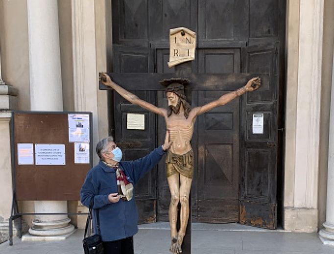 A woman wearing a protective mask touches the crucifix outside the village church on March 16 in Brescello, Italy. The Italian government continues to enforce nationwide lockdown measures to control the coronavirus spread.