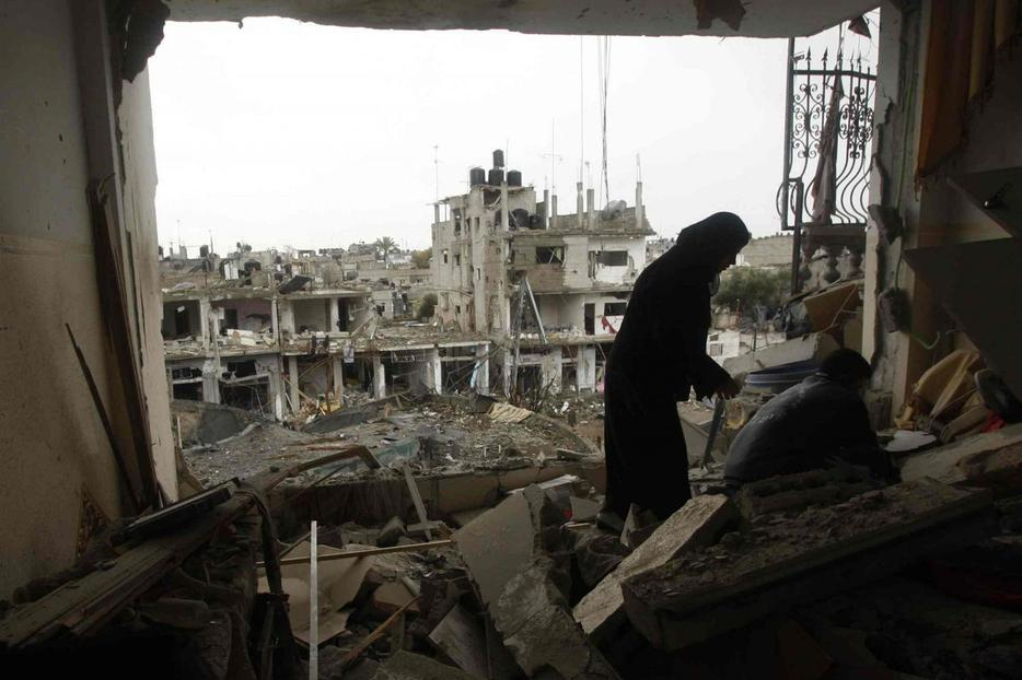 A Palestinian woman surveys her damaged house after an Israeli airstrike Jan. 1 in Gaza.