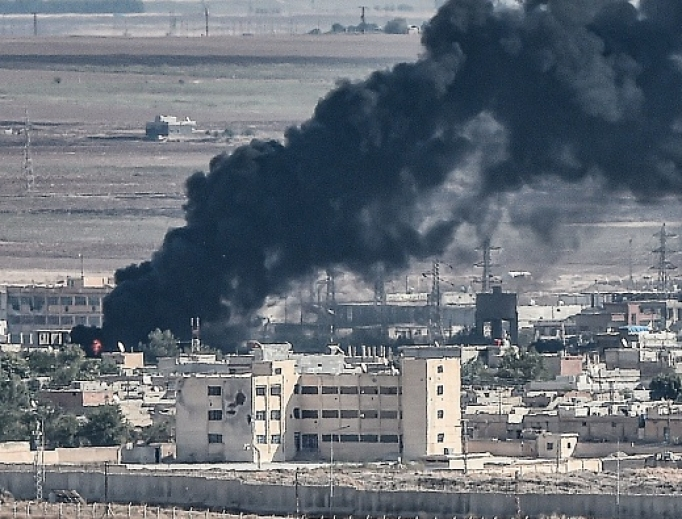 This picture, taken Oct. 13, from the Turkish city of Ceylanpinar shows smoke rising from the Syrian border town of Ras al-Ain as fighting rages along the border on the fifth day of a Turkish offensive in Syria against the Kurdish People's Protection Units (YPG) that has provoked an international outcry and left dozens of civilians and fighters dead.