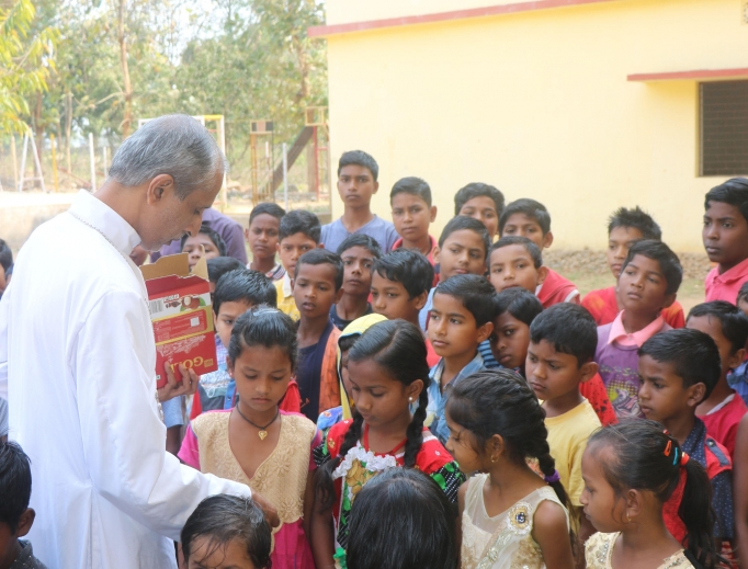 Bishop Jacon Muricken distributes sweets to children at a Catholic school at Barakhama in Kandhamal during a visit in March, 2019.