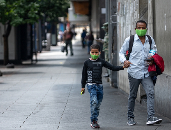 Father and son holding hands wearing face masks walk the streets during the quarantine decreed by Nicolas Maduro in Caracas, Venezuela, March 24, 2020.