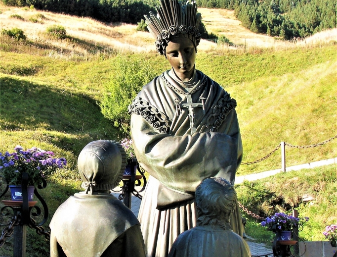 Mary appeared in the French Alps in 1846, requesting conversion ahead of famine, as commemorated in statues; pilgrims find solace in the basilica in the hills.