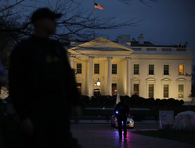Members of the U.S. Secret Service stand guard outside the White House on March 6, 2017. Activists staged a protest against President Donald Trump's second Executive Order banning travel from certain Muslim-majority countries.