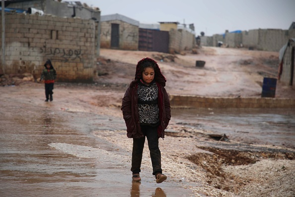 A Syrian girl walks in the mud near makeshift shelters following heavy rains, at a camp for displaced people in the village of Atme, in Syria's mostly rebel-held northern Idlib province Jan. 8.