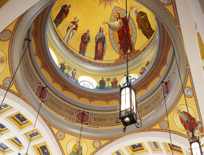 Above, the cathedral dome rises 144 feet into the air. Inside it are murals of the Sacred Heart flanked by Mary and St. Joseph, along with several other saints, ancient and modern. Below, the dedication Mass is underway.