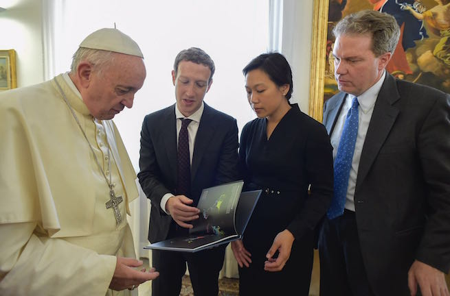 Zuckerberg and Chan presenting a gift to the Pope, accompanied by Vatican spokesman, Greg Burke.
