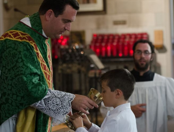 Above, Bishop Steven Lopes provides the Precious Blood at first Communion for St. Alban's Catholic Church, an ordinariate parish in Rochester, N.Y. Below, children receive first Communion at St. Joseph Oratory in Detroit.