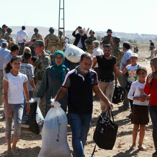 Residents of Kobane, Syria, flee across the Turkish border in fear of attacking Islamic State forces.