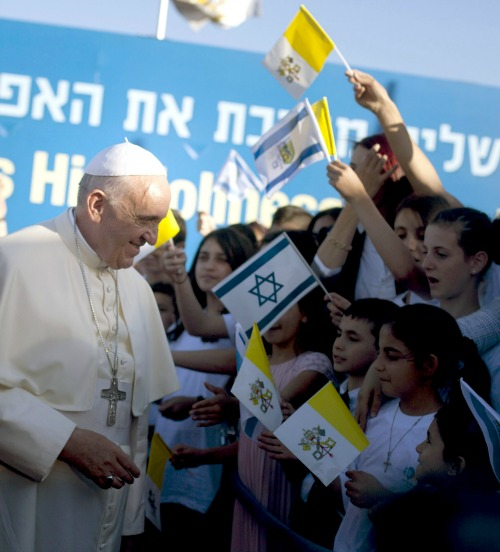 Pope Francis speaks to children waving papal  and Israeli flags at the beginning of his visit to Jerusalem on May 25.