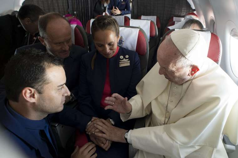 Above, Pope Francis marries flight attendants Paula Podest and Carlos Ciuffardi during his flight from Santiago to Iquique, Chile, Jan. 18. Below: Podest and Ciuffardi. Also below, the marriage certificate was drawn up by cardinals who accompanied the Pope on the flight.