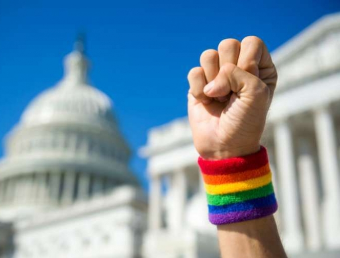 Hand wearing gay pride rainbow wristband making a power fist gesture in front of the US Capitol Building in Washington, DC.
