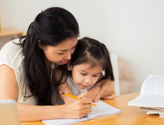 Mother teaching her young daughter how to write.