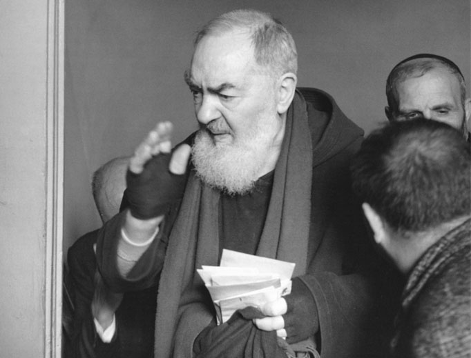 Padre Pio, bearing the stigmata, blesses the faithful.