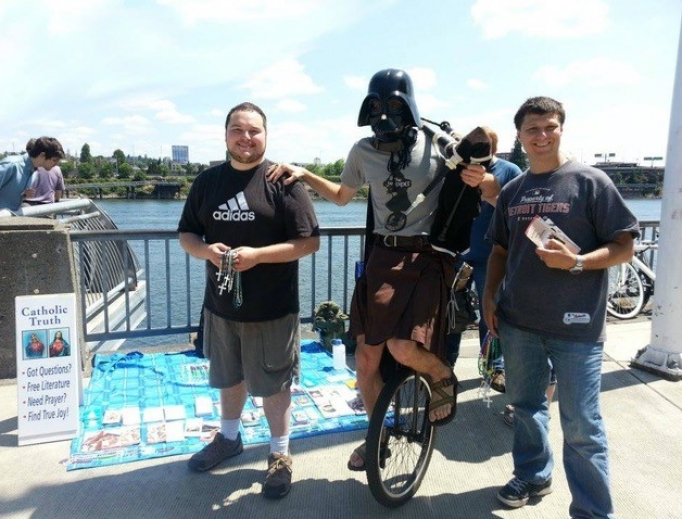 Steve Dawson (r) chats with 'Darth Vader.' Below, he further shares the Gospel, as does Archbishop Allen Vigneron.