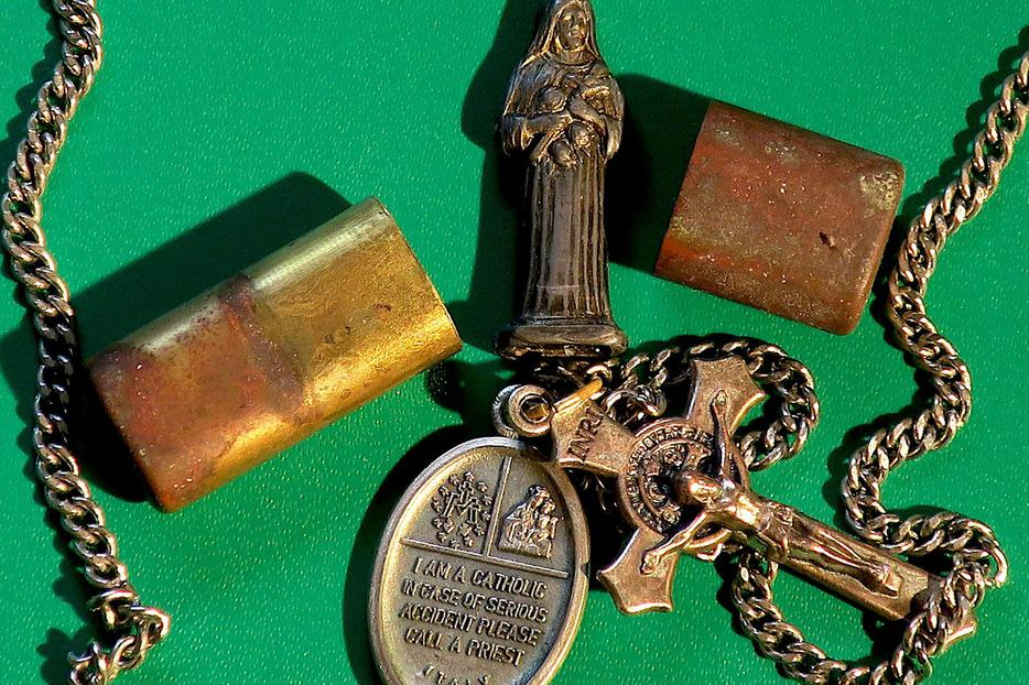 A pocket shrine, a holy medal, and a St. Benedict crucifix.
