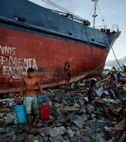 Residents carry water Nov. 18 past a ship that was thrown into the street by Typhoon Haiyan in Tacloban, Philippines.