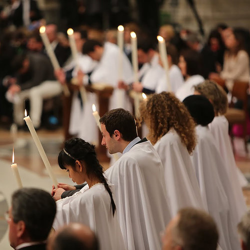 WELCOME HOME! Catechumens receive candles at the Easter vigil Mass before receiving the sacraments in St. Peter's Basilica.