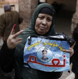 A woman shows her ink-stained fingers, evidence she has voted in Egypt's constitutional referendum, and holds a poster of General Abdel Fattah al-Sisi at a Cairo polling booth on Jan. 14.