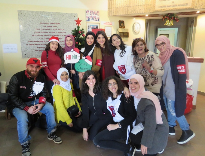 """Above, volunteer youth from the Order of Malta Lebanon, a Catholic organization, and """"Who Is Hussain?"""" a Shiite Muslim organization, gather at the order's community health center in the Ain El Remmaneh suburb of Beirut Dec. 9 before heading out to decorate the homes of poor elderly Christians for Christmas. Below, volunteers pose with Gabriel and his sons, whom they visited Dec. 9 to decorate their Christmas tree."""
