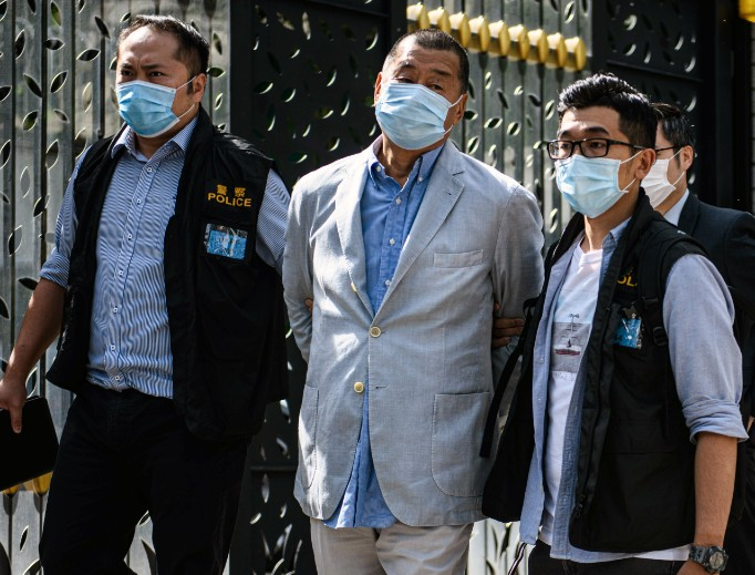 Hong Kong police lead pro-democracy media mogul Jimmy Lai (c), 72, a Catholic, away from his home after he was arrested under the new national security law in Hong Kong Aug. 10. Chinese police also raided his newspaper offices in a deepening crackdown on dissent.