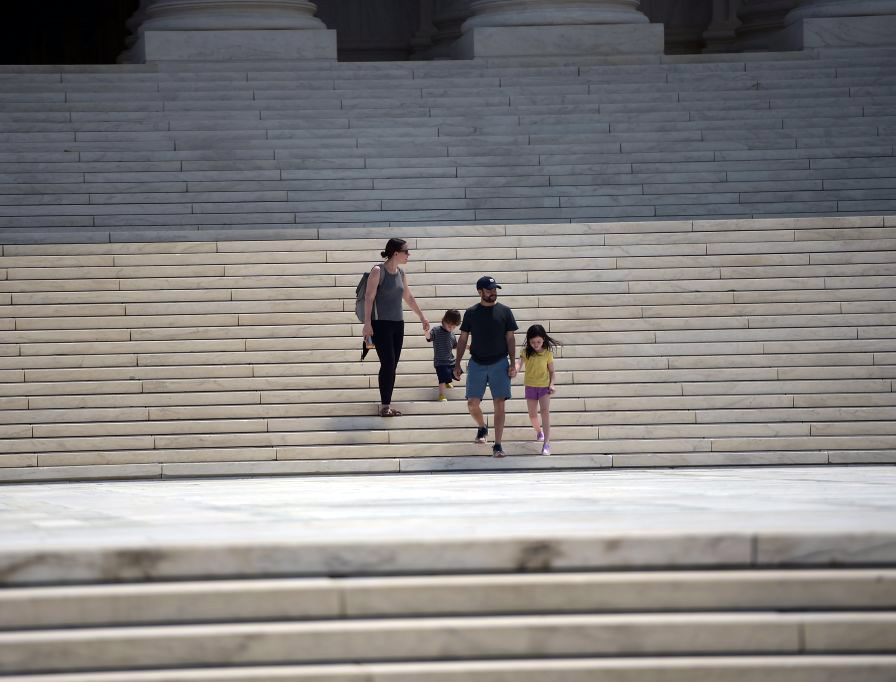 A family walks down the steps of the U.S. Supreme Court building in Washington, D.C., on Monday.