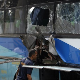 A member of a forensic team examines damage on a passenger bus after an explosion along a major road in Manila, Philippines, Jan. 25. The blast killed five people and wounded 12 others, reported the Asian Church news agency UCA News.