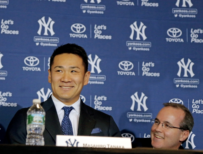 Above, George Rose (r) during pitcher Masahiro Tanaka's introductory news conference with the Yankees in 2014. Below, Rose (c) with his son, Sean, and wife, Carrie, in front of the sarcophagus of Blessed Father Michael Sopocko, above which hangs his portrait. This was taken in April of this year during a pilgrimage to the Divine Mercy Sanctuary in Bialystok, Poland. The Roses are seeking the blessed's intercession for George's cancer.