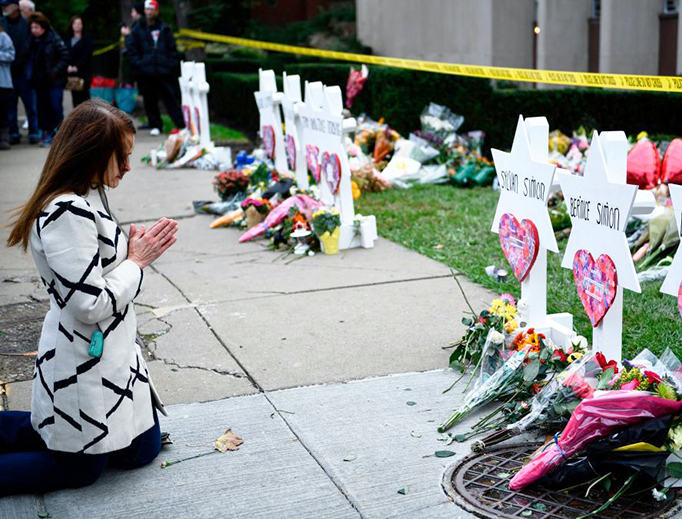 People pay their respects Oct. 29 at a memorial outside the Tree of Life synagogue after a shooting there left 11 people dead in the Squirrel Hill neighborhood of Pittsburgh, Pennsylvania, on Saturday.