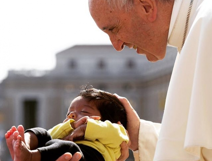 Pope Francis blesses a baby in St. Peter's Square.