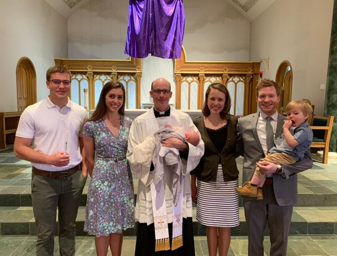 Above, a new member of the Church is welcomed: L-R, godparents Charlie and Rebecca Liffrig are shown with Father Bill Ruelle, holding newly baptized Micah Desilets, and his parents, Kristen and Christoper, and big brother, Jude. Below, John, the youngest son of Carrie Gress, was baptized last month.