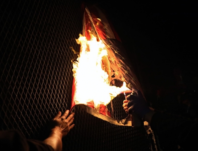 An American Flag is burned as protesters gather in front of the Mark O. Hatfield federal courthouse in downtown Portland as the city experiences another night of unrest on July 25, 2020 in Portland, Oregon. For over 55 straight nights, protesters in downtown Portland have faced off in often violent clashes with the Portland Police Bureau.