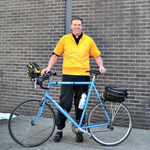 Father James Sullivan, shown with his 25-year-old bike, wears his clerics on rides.